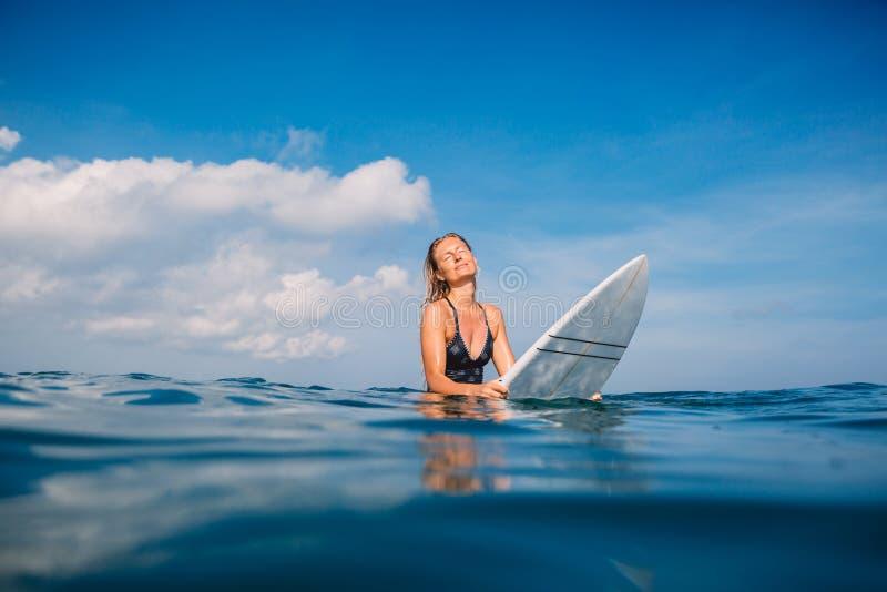 Beautiful surfer woman in swimwear with surfboard. Surfer with surfboard in tropical ocean. royalty free stock photos