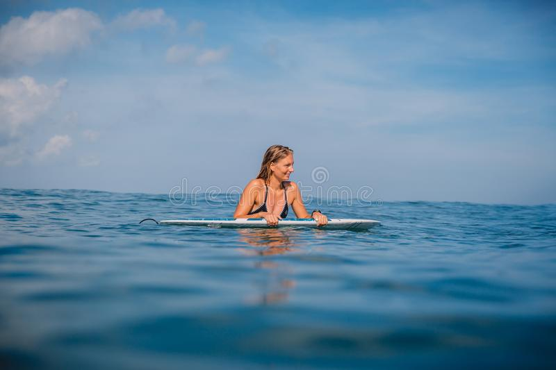 Beautiful surfgirl relaxed with surfboard and watching at waves. Surfer with surfboard. royalty free stock image