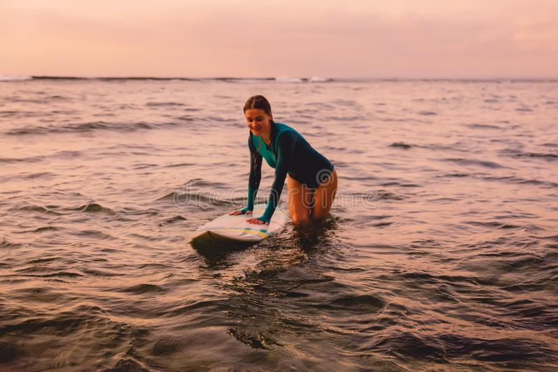 Beautiful surfgirl on a surfboard in ocean. Beautiful surfgirl on a surfboard floating in ocean. Surfing at sunset stock image
