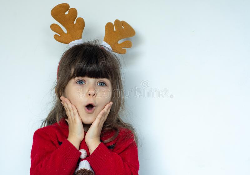 Beautiful surprised child in Santa Claus hat, Emotions. Funny Laughing child Portrait. Christmas sale. Beautiful surprised child in Santa Claus hat, Emotions royalty free stock photography
