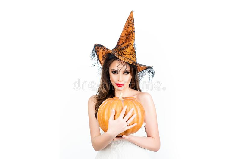Beautiful surprised girl in witch hat costume and holding pumpkin - isolated on white background. Celebration autumn stock image