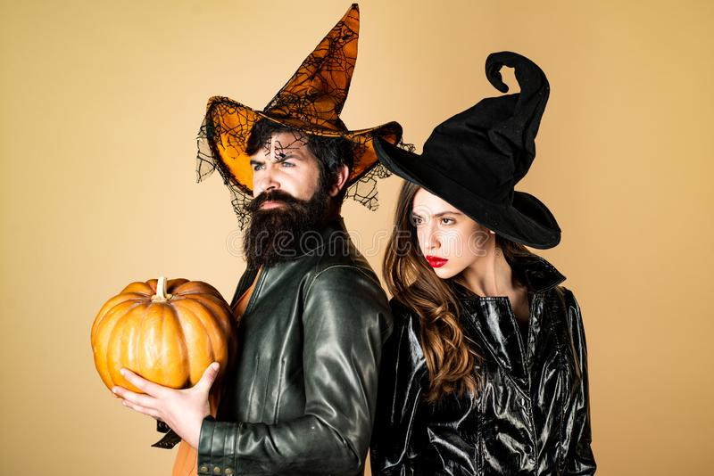Beautiful surprised woman in witch hat and costume - showing products. Woman witch with Pumpkin and Handsome bearded man royalty free stock photos