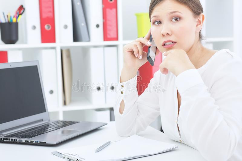 Young beautiful surprised business woman talking on the mobile phone sitting at office. royalty free stock photos