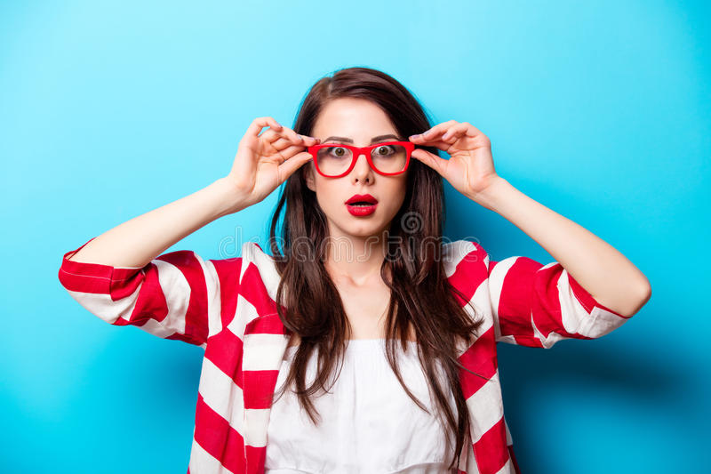 Beautiful surprised young woman in glasses standing in front of. Wonderful blue background stock photography