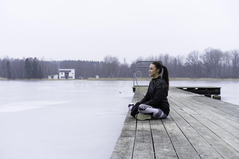 Beautiful Swedish caucasian fitness teen girl sitting on wood bridge outdoor in winter landscape stock photos