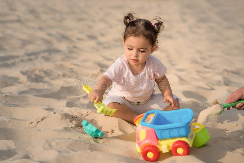 Beautiful sweet Baby girl playing on the sandy summer beach near the sea. Travel and vacation with children. stock photo