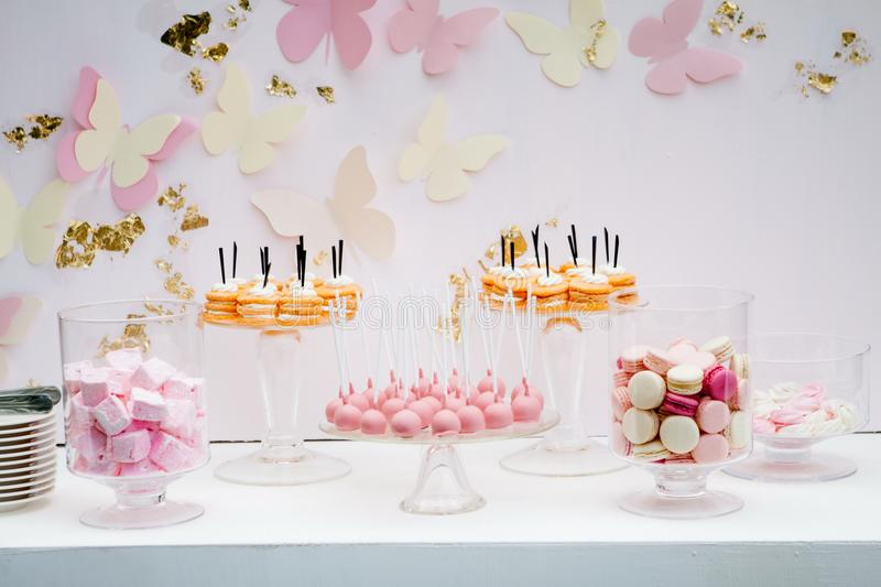 A beautiful sweet dessert with an airy white kem. Portion cakes. Pink white crimson macaroons. Pink marshmallow. Candy bar stock image