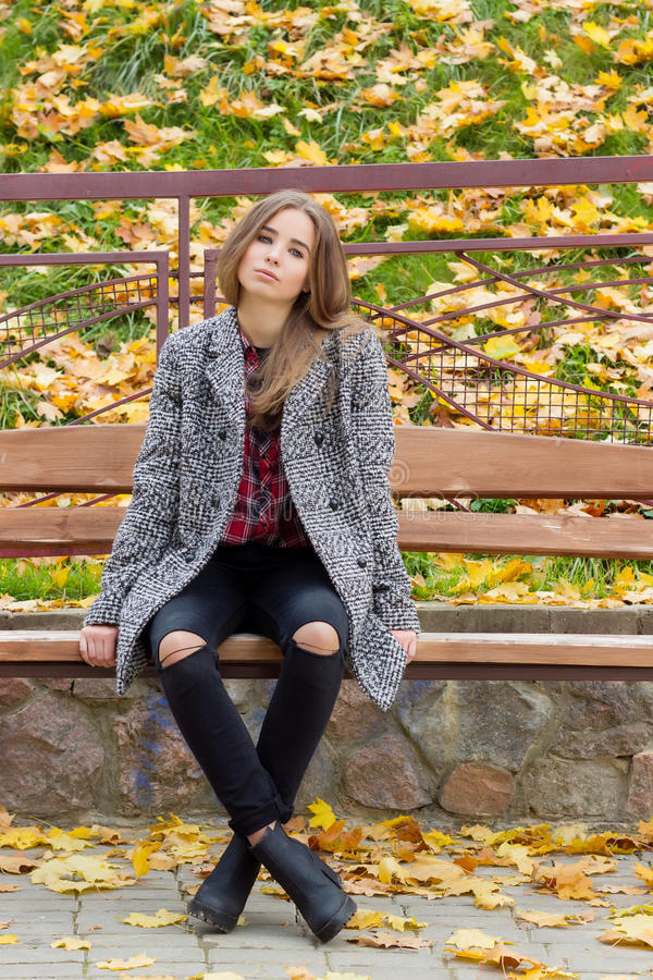 Beautiful sweet girl with the big sad eyes in coat sitting on the bench in the fall among the fallen yellow leaves autumn bright royalty free stock images