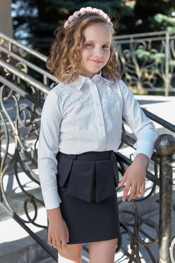 Beautiful sweet girl schoolgirl in school uniform outside on a sunny day with curly hair and a wreath of delicate roses in her hai stock photos