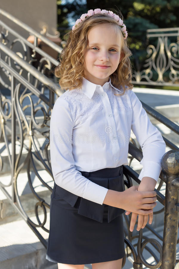 Beautiful sweet girl schoolgirl in school uniform outside on a sunny day with curly hair and a wreath of delicate roses in her hai. R stock photography