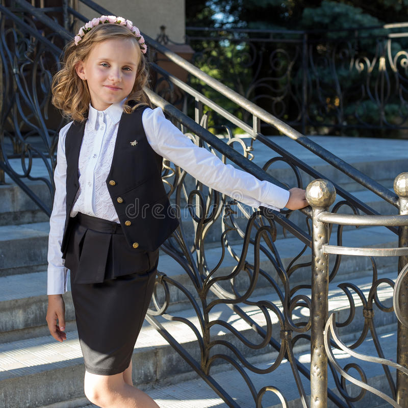 Beautiful sweet girl schoolgirl in school uniform outside on a sunny day with curly hair and a wreath of delicate roses in her hai. R royalty free stock image