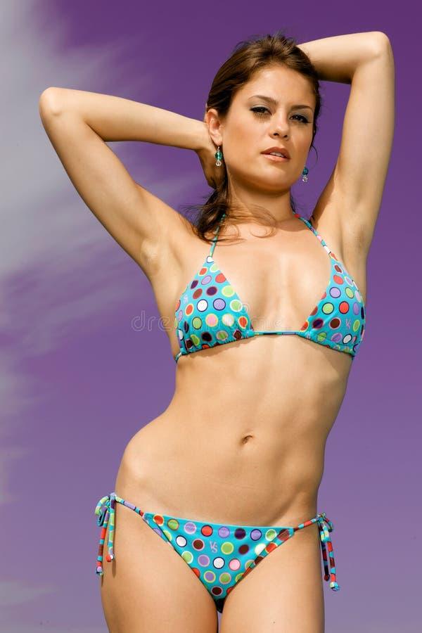 Beautiful swimsuit model against a purple sky. stock photos