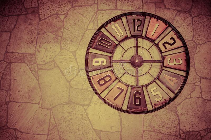 Beautiful symbolic clock on a wall with a stone texture. Toned photo with vignetting.Place for text. Artistic background stock photo