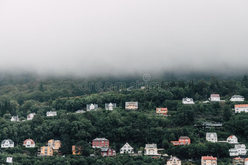 Beautiful symmetric shot of colorful houses on a foggy hill royalty free stock image