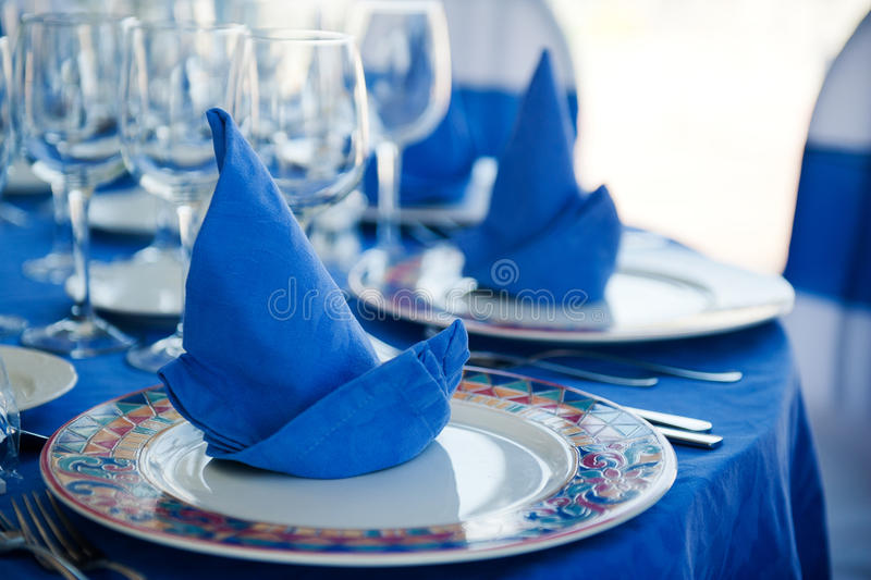 Beautiful table with blue napkins. Wedding Serving a beautiful table with blue napkins royalty free stock photography