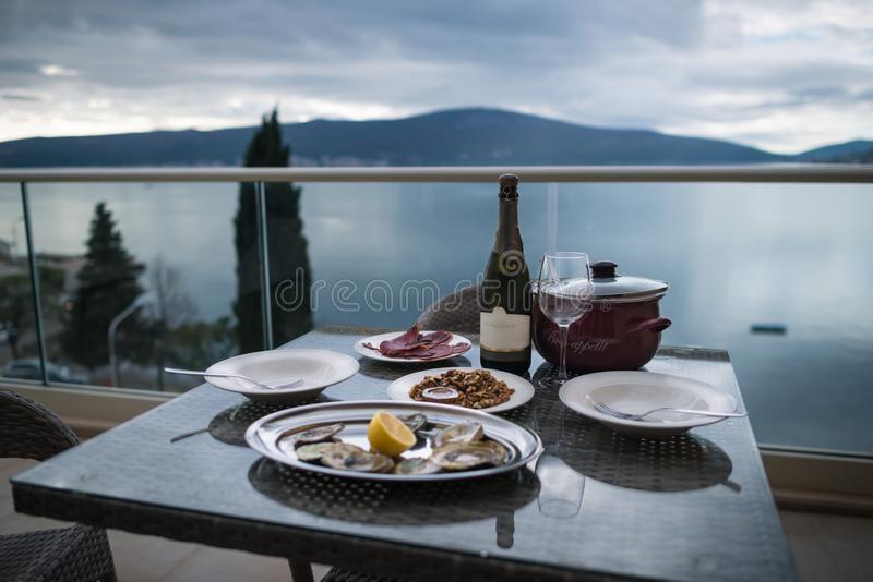 Beautiful table with local food and wine on the home balcony. Focus on the bottle. Background of sea and mountains. Oysters with lemon, meat, snacks and bottle royalty free stock images