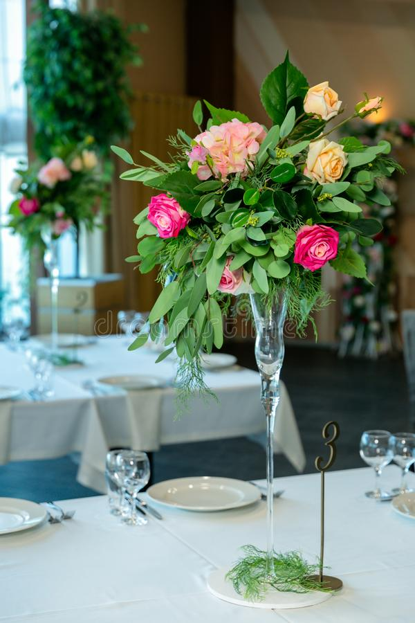 Beautiful table setting with crockery and flower arrangement in a vase on a high stem for a party, wedding reception or other royalty free stock photo