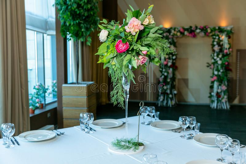Beautiful table setting with crockery and flower arrangement in a vase on a high stem for a party, wedding reception or other stock images