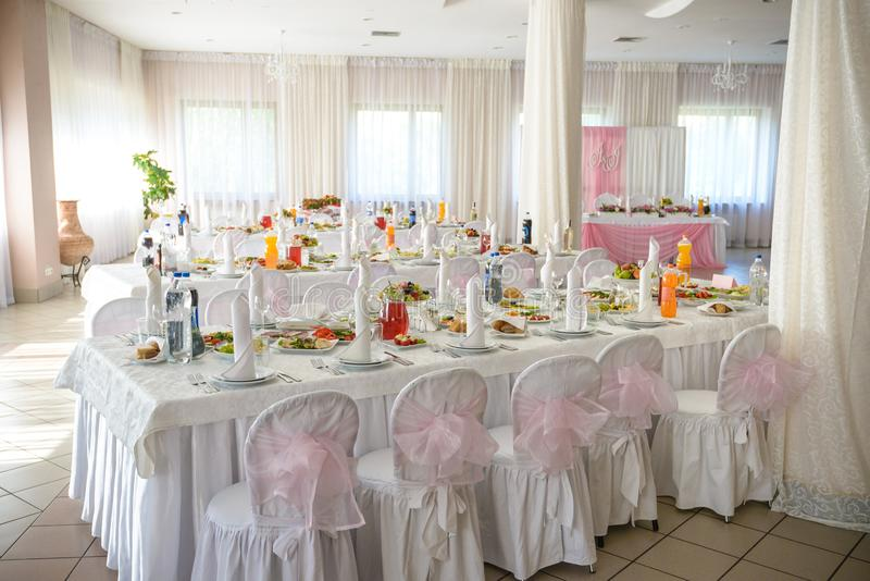 Beautiful table setting with crockery and flowers for a party, wedding reception or other festive event. Glassware and cutlery for stock images