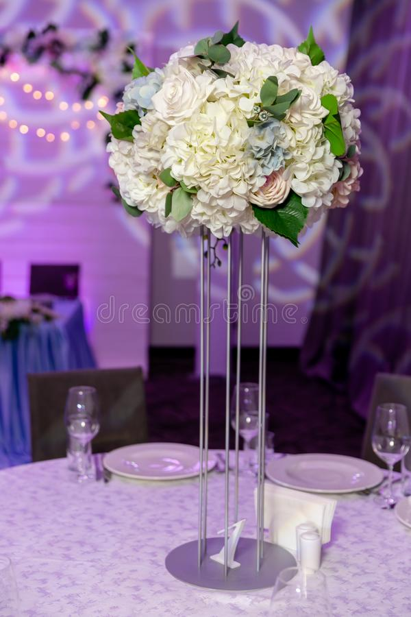 Beautiful table setting with crockery and white flower arrangement in a vase on a high stem for a party, wedding reception or stock image