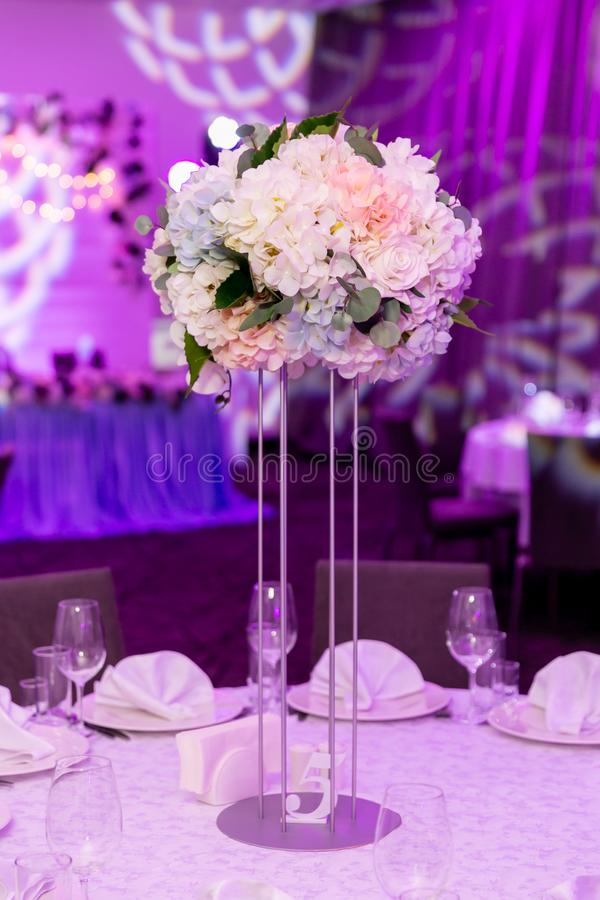 Beautiful table setting with crockery and white flower arrangement in a vase on a high stem for a party, wedding reception or stock images