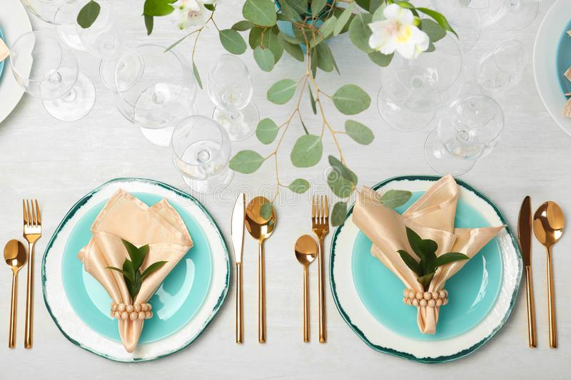 Beautiful table setting with cutlery, glasses, napkins and plates on grey background. Top view royalty free stock photo
