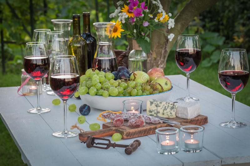 Beautiful table with wine and candles in garden at dusk. In summer royalty free stock photos
