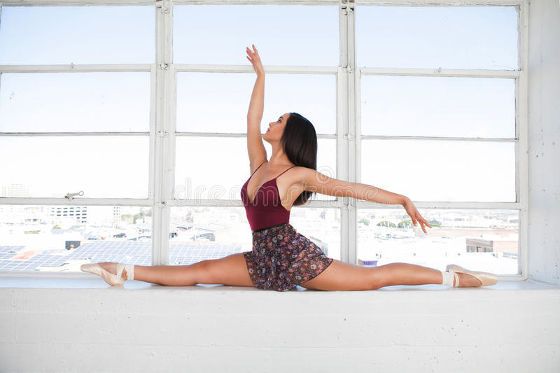 Beautiful talented woman doing the split at window background. Working out royalty free stock photo