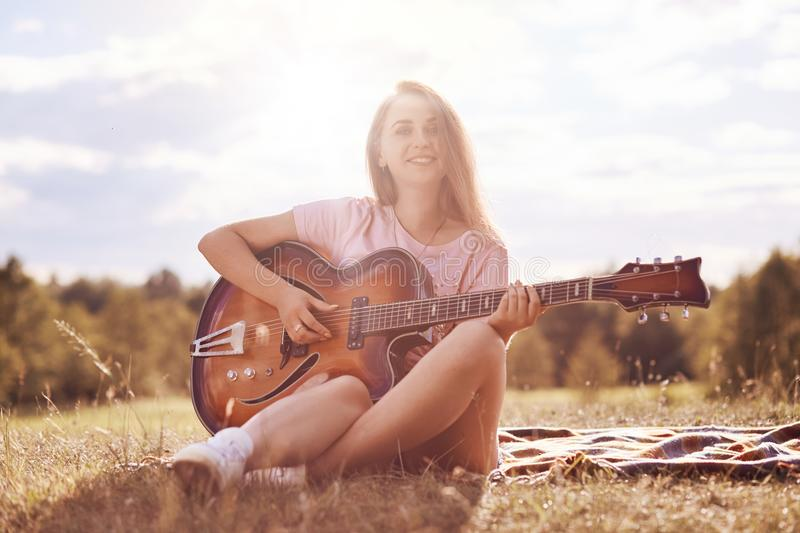 Beautiful talented young female musician plays acoustic guitar, has gentle smile on face, sits on green grass of meadow, has joyfu stock photography