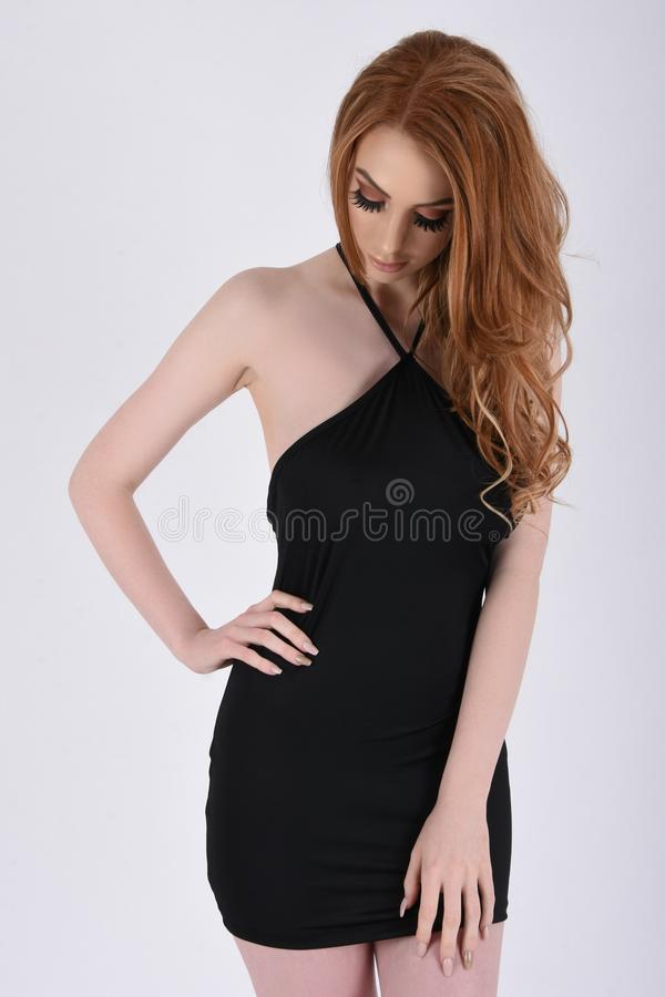 Sexy, Busty Redhead in a Short, Tight, Black, Party Dress. Beautiful, tall, slim, busty redhead model dressed in a short, sexy, tight, black party dress royalty free stock image