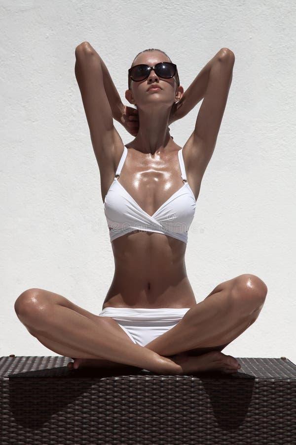 Beautiful tan female model posing in bikini and sunglasses. Against white wall stock images
