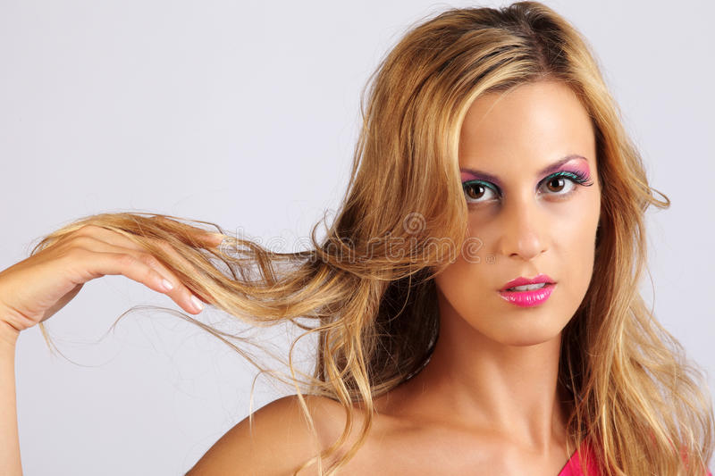 Beautiful tanned girl with long blond hair. Onwhite background royalty free stock images