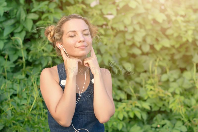 Beautiful tanned happy teen girl listening to music in headphones in nature in the summer. royalty free stock images