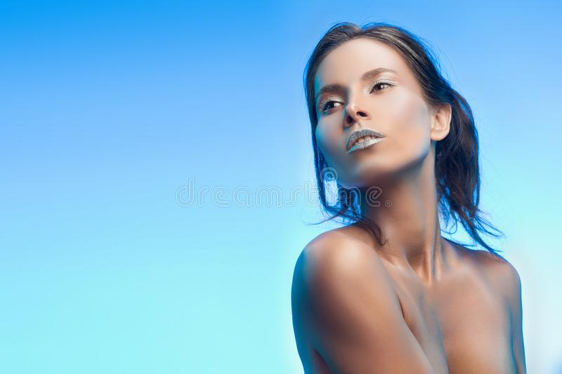 Beautiful tanned mixed asian-caucasian girl with silvery make-up. Advertising and Commercial Design, Fashion. Sku blue gradient background. Healthy clean skin stock image