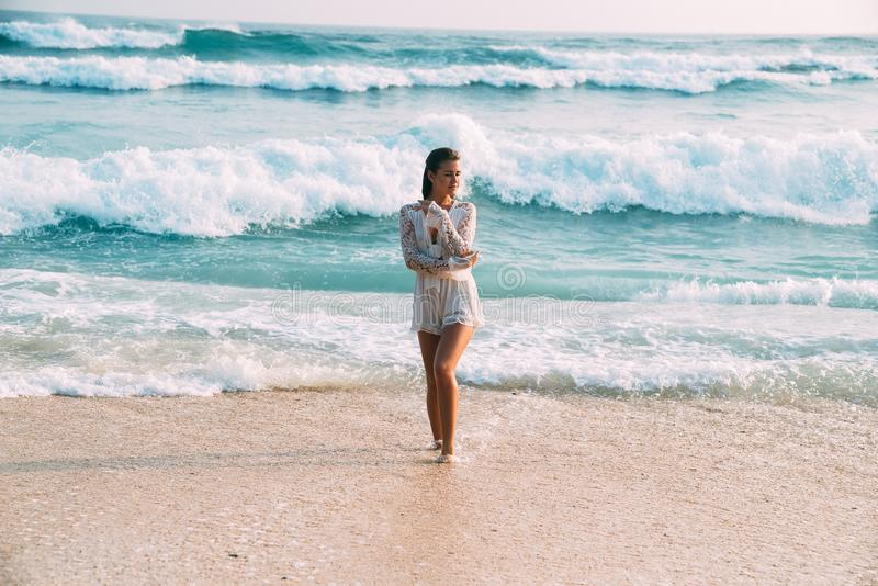 A beautiful tanned, shining young European woman in a snow-white suit is standing on the beach against a background of royalty free stock photos