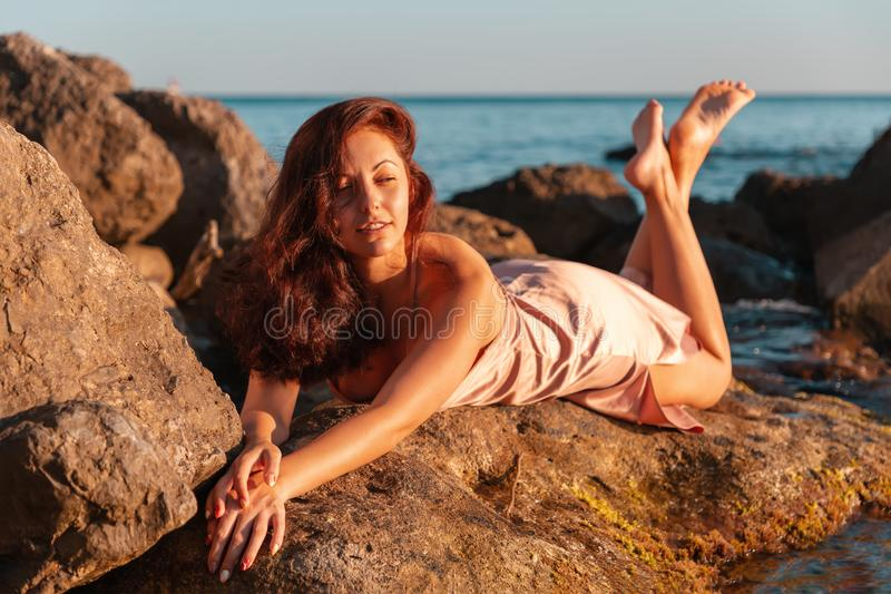 A beautiful tanned woman in her underwear lies on the coastal rocks. The sea in the background. Sunset royalty free stock image