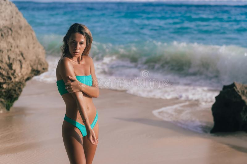 Beautiful tanned woman in separate swimsuit posing on beach and looking towards ocean royalty free stock images