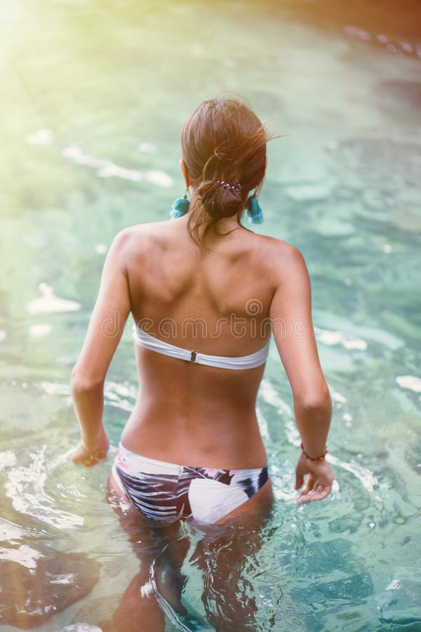 A beautiful tanned woman swims in the sea, ocean or pool. The view from the back. Tint and illumination royalty free stock photos