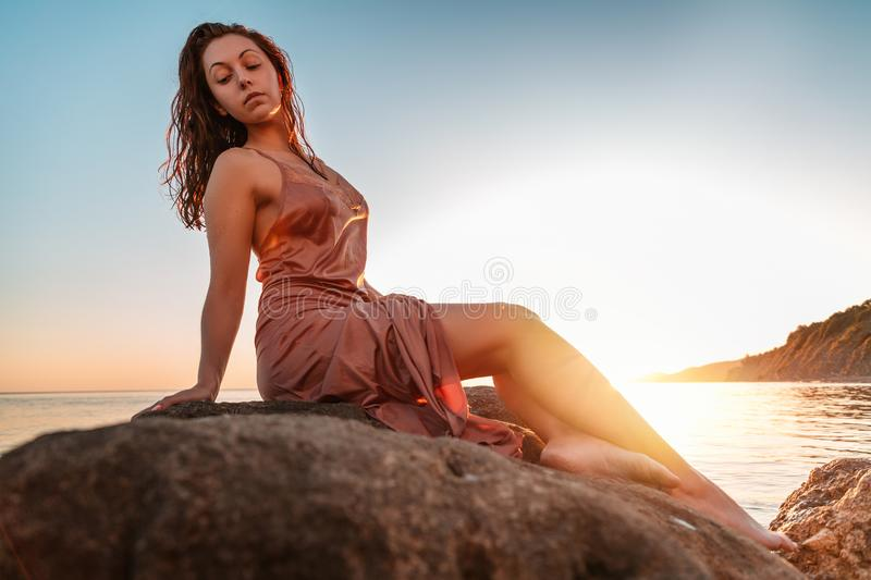 Beautiful tanned woman in underwear sitting on the coastal rocks. Sea and sunset in the background. Copy space stock photo
