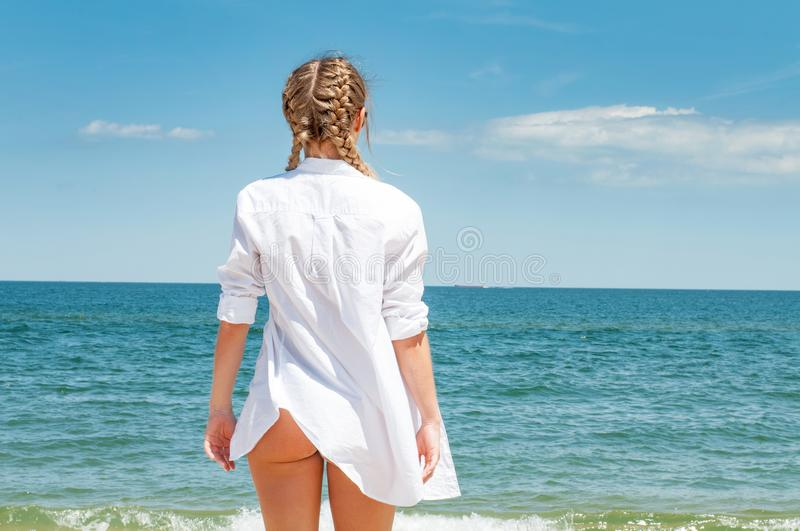 Beautiful tanned woman in white shirt looking at ocean, on the beach stock image