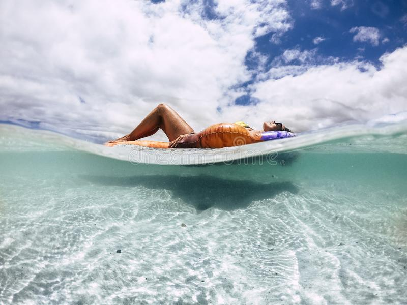 Beautiful tanned young woman lay down and relax on a trendy inflatable lilo in a paradise beach with sand and clear blue water - stock image