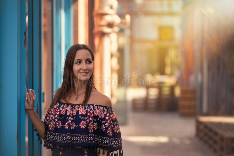 Beautiful tanned young woman posing on the street. Vintage and Oriental flavor stock image