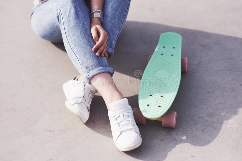 Beautiful teen female skater sitting on ramp at the skate park. Concept of summer urban activities stock images
