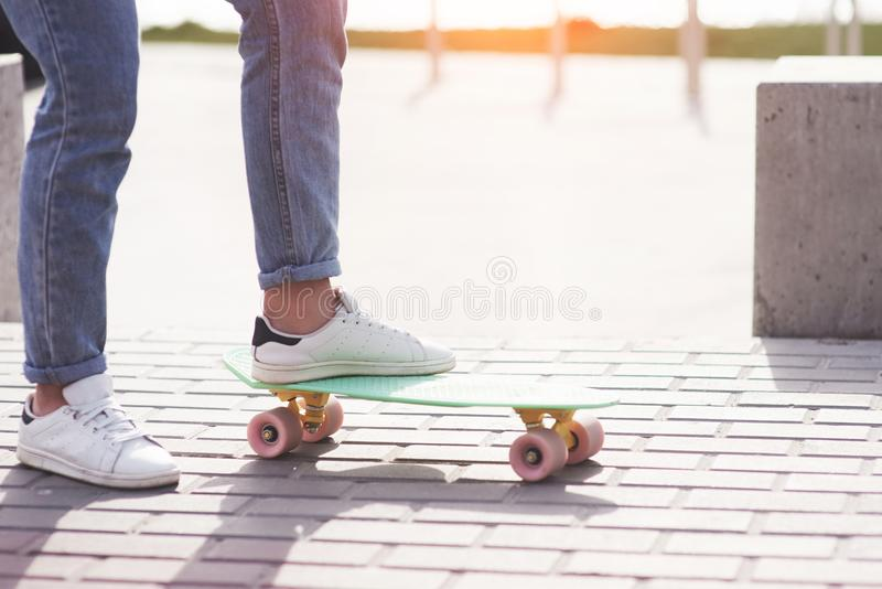 Beautiful teen female skater sitting on ramp at the skate park. Concept of summer urban activities royalty free stock image