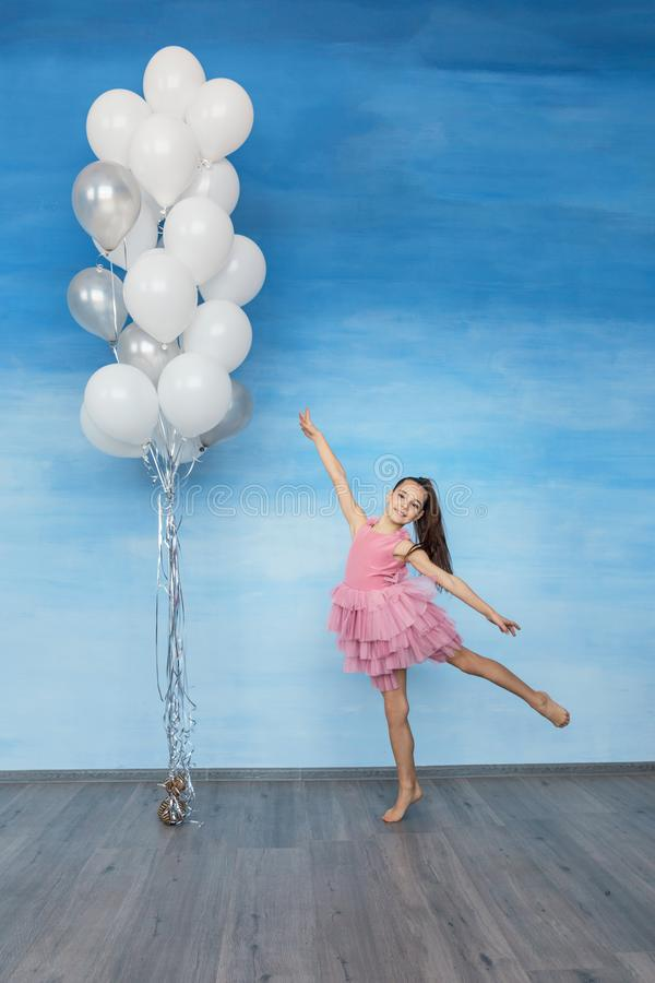 A beautiful teen girl with brown hair in a pink dress is standing against a blue sky background and holding a lot of balloons. stock photos