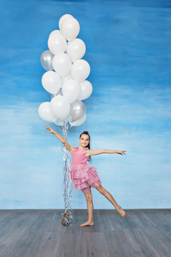 A beautiful teen girl with brown hair in a pink dress is standing against a blue sky background and holding a lot of balloons. stock images