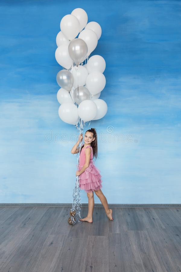 A beautiful teen girl with brown hair in a pink dress is standing against a blue sky background. And holding a lot of balloons royalty free stock images