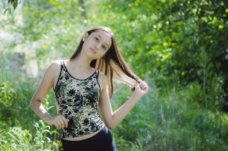 Beautiful teen girl brunette with long hair on a background of green trees. Close-up stock images