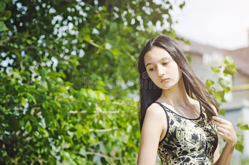 Beautiful teen girl brunette with long hair on a background of green trees royalty free stock images