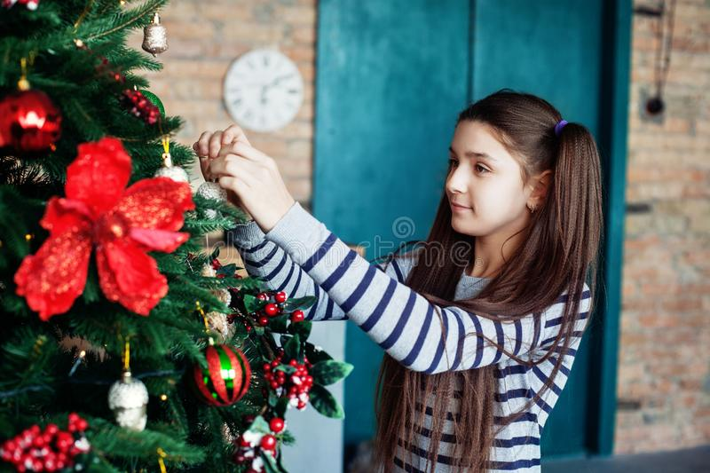 Beautiful teen girl decorates the Christmas tree in the house. T royalty free stock images